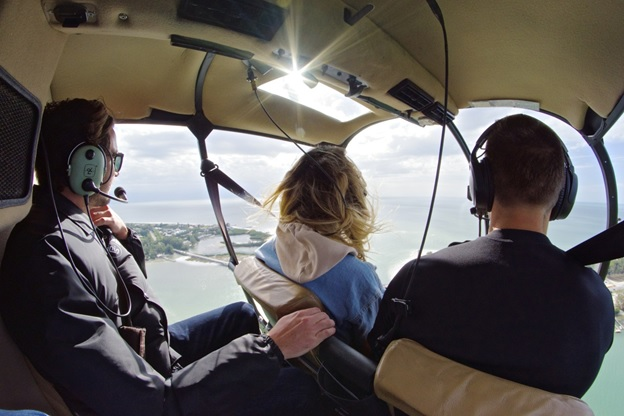 People in a helicopter tour flying above the ocean