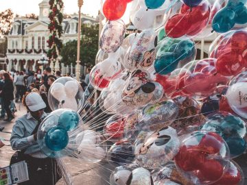 Person holding Disney-themed Balloons