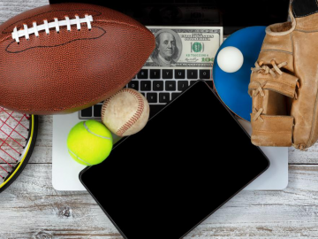 Sports equipment, a $100 bill, and a tablet on a laptop illustrating the concept of online sports betting.