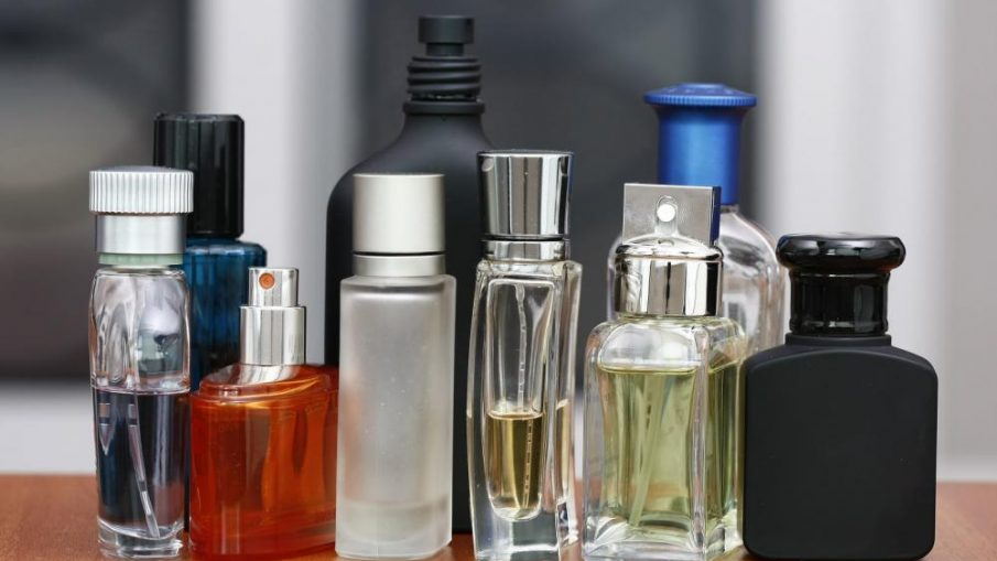 Various cologne and perfume bottles on wooden table