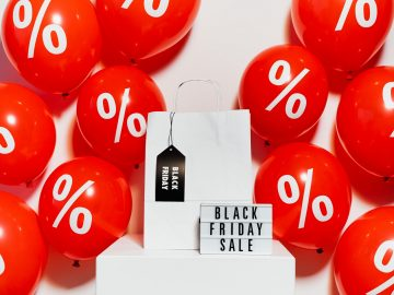A Black Friday sale sign, a white shopping bag with a black tag that says Black Friday, and red balloons with percentage signs on them against a white background