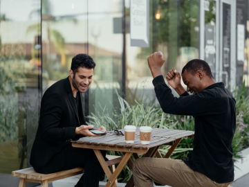 Two men celebrating a win after opening a betting account online
