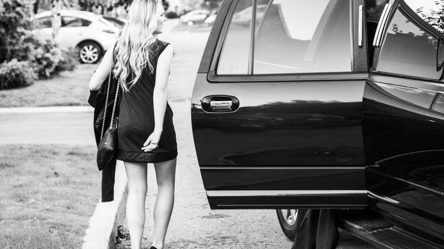 Woman getting into the back of a black limo, a gift from her partner