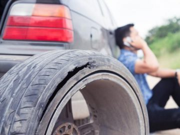 man with blown tire calling for roadside assistance