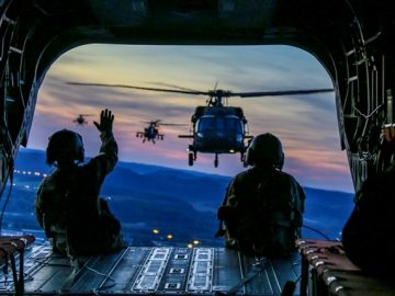 military waving from inside the helicopter