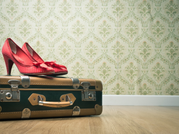 Red vintage heels on a green suitcase