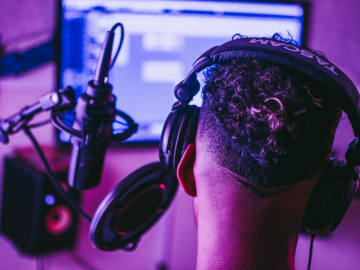 A person under purple lights with shaved sides, a headset, computer, and mic is usingrecording software and audio editing software