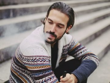 A person vaping on the stairs