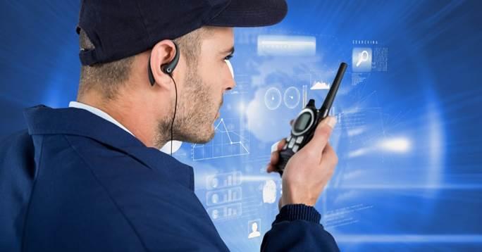 Security guard using radio against screen