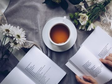 A person reading books and drinking tea