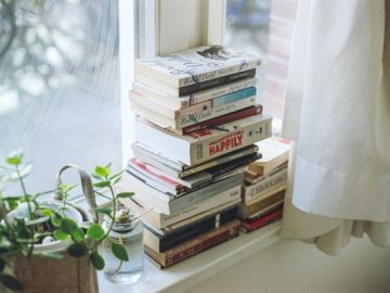 A pile of books on the window sill