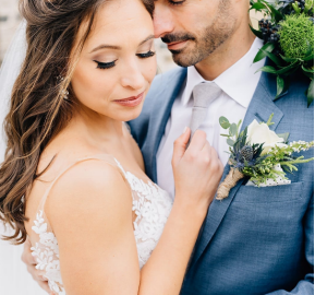 An expert wedding photographer in Virginia has captured a picture of a groom in a blue suit with a white dress shirt and grey tie who's posing underneath some plants and embracing his soon-to-be-wife as they both have their eyes closed