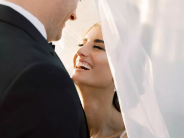 A top wedding photographer in Virginia captures a tender moment between the bride and groom in which the bride is laughing and looking up at the groom lovingly, who is smiling back down at her with her veil, creating a beautiful frame for the photo