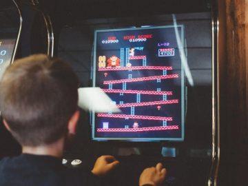 Little boy playing a Donkey Kong game on an arcade machine