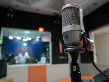 A grey microphone in a music recording studio
