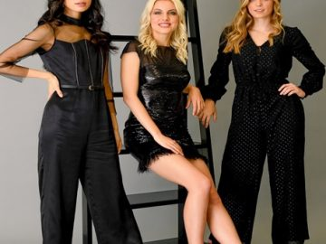 Three Women, two in a Black Jumpsuit, and One in a Black Minidress, Posing in Front of a Ladder