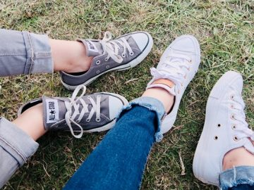 Two Pairs of Legs, resting on a Grassy Surface, Clad in Sneakers and Cuffed Jeans