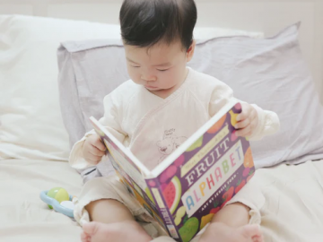 A toddler reading a picture book
