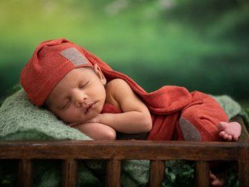 a newbornsleeping with their hands under their chin