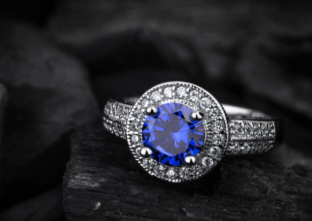 jewelry ring witht big blue sapphir on black coal background